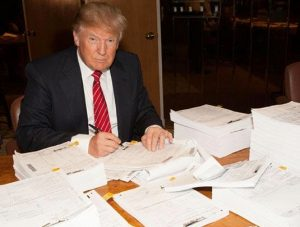 Donald Trump signing his tax returns