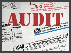 The word AUDIT and various tax forms.